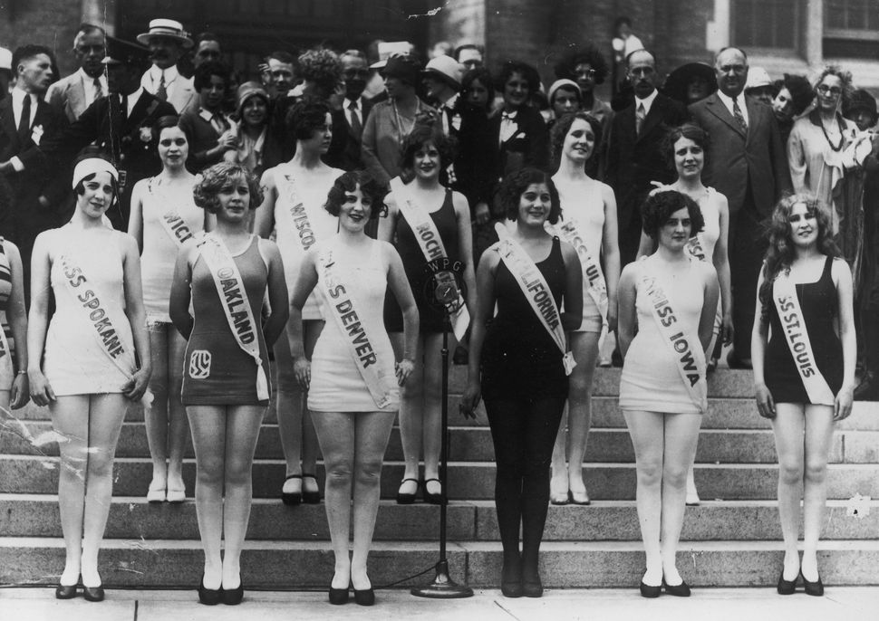 Miss America contestants, representing their home cities and states, pose in one-piece bathing suits and sashes on the steps