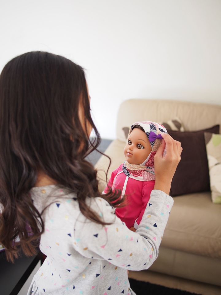 A young girl plays with a Salam Sisters doll named Maryam.