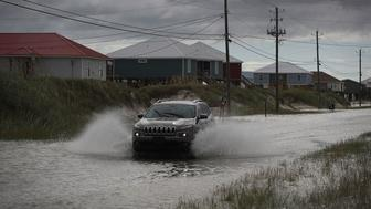 DAUPHIN ISLAND, AL - SEPTEMBER 04:  A vehicle drives along a flooded street caused by the approaching Tropical Storm Gordon on September 4, 2018 in Dauphin Island, Alabama.  Gordon heads for the northern Gulf Coast area as a strong tropical storm and could possibly strengthen into a Category 1 hurricane.  (Photo by Joe Raedle/Getty Images)