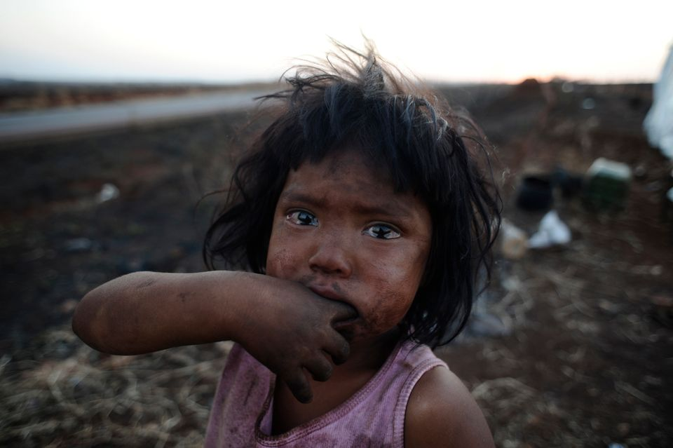 A Guarani Kaiowa Indian girl, Sandriely, in front of her hut near Dourados in Mato Grosso do...
