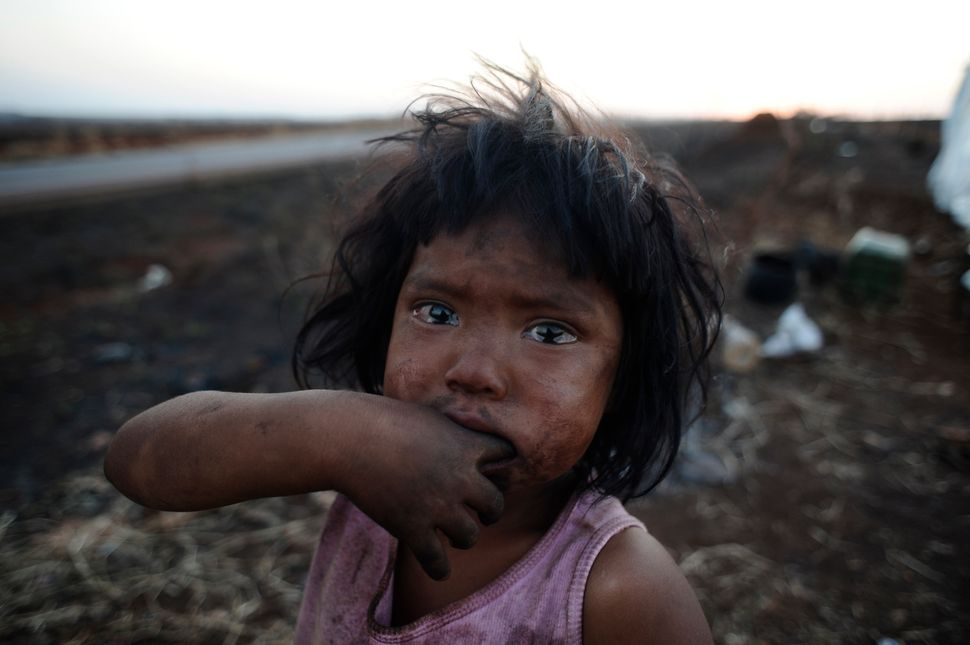 A Guarani Kaiowa Indian girl, Sandriely, in front of her hut near Dourados in Mato Grosso do Sul state, Brazil, whi