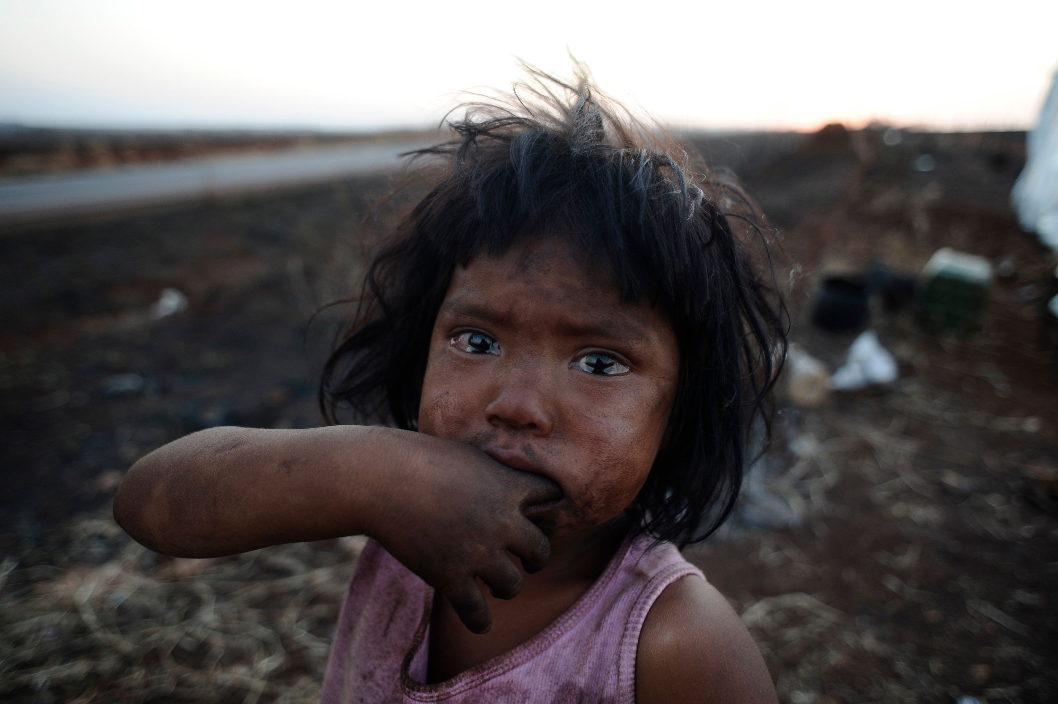 Guarani Kaiowa Indian girl Sandriely cries in front of her hut destroyed by a fire set by an unknown arsonist in their makeshift camp squeezed between highway BR 463 and their ancestral land called Tekoha Apika'y, where they have been since 2009 when they last failed to take back the land from farmers, near Dourados, Mato Grosso do Sul state, August 31, 2013. The Guarani tribe is immersed in a bloody conflict with farmers over possession of their ancestral land that has characteristics of a territorial war, in spite of Brazil's indigenous policy being considered one of the most progressive in the world. The conflict highlights the risks being run by an agricultural superpower whose leftist government is trying to sort out centuries of ethnic disputes over ownership of the land from which much of the nation's wealth sprouts. Picture taken August 31, 2013. REUTERS/Lunae Parracho (BRAZIL - Tags: POLITICS ENVIRONMENT SOCIETY CIVIL UNREST TPX IMAGES OF THE DAY)  ATTENTION EDITORS: PICTURE 20 OF 30 FOR PACKAGE 'BRAZIL'S ANCESTRAL LAND WAR'. TO FIND ALL IMAGES SEARCH 'GUARANI TRIBE'