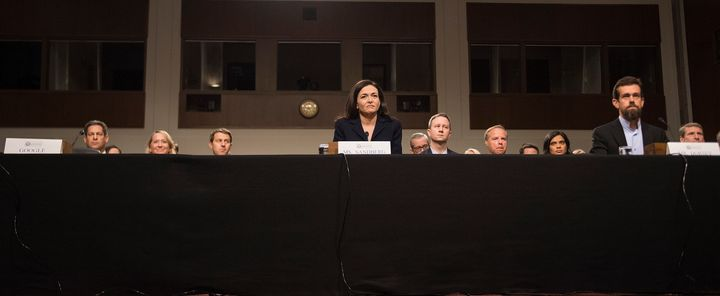 An empty chair on the left marks the absence of anyone from Google as Facebook COO Sheryl Sandberg and Twitter CEO Jack