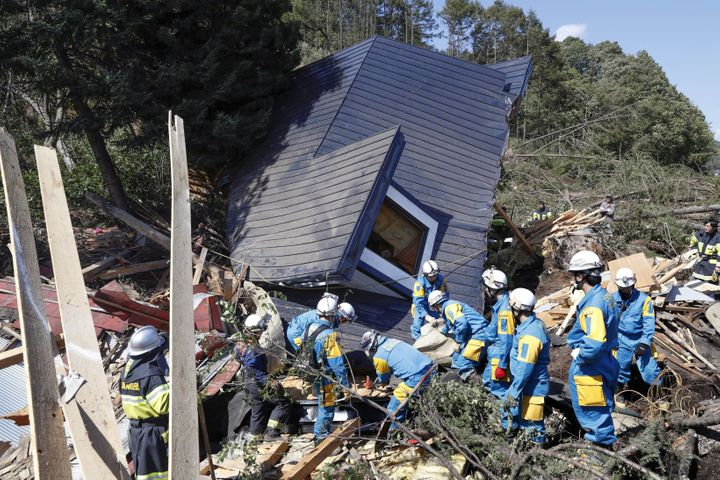 Rescue workers search the rubble for survivors after an earthquake triggered a landslide in Atsuma town, Hokkaido, Japan on T