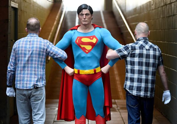 Prop Store employees with a Superman costume worn by Christopher Reeve from the 1978 and 1980 films.