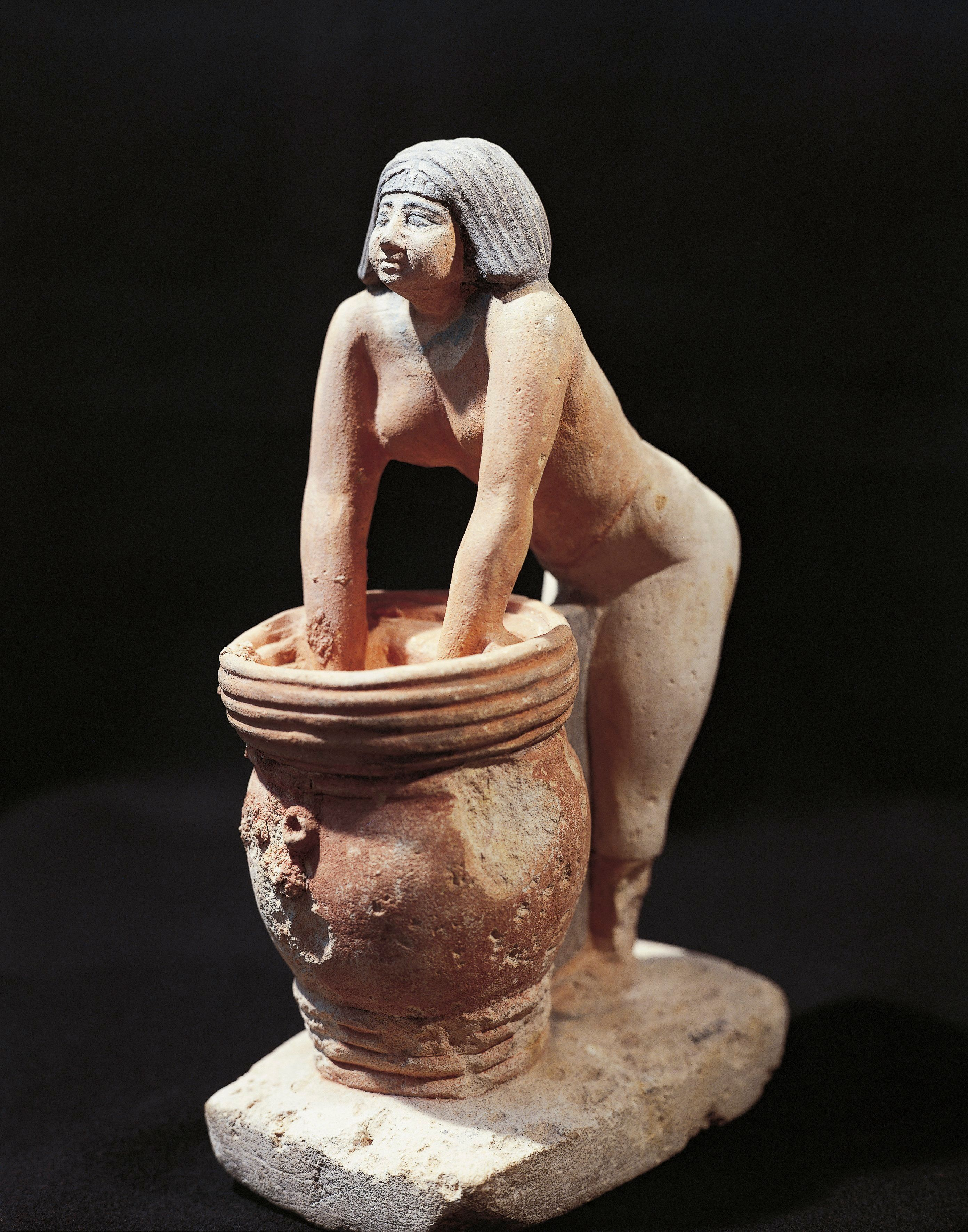 Circa 1900: A painted limestone statuette of a woman making beer in Egypt.