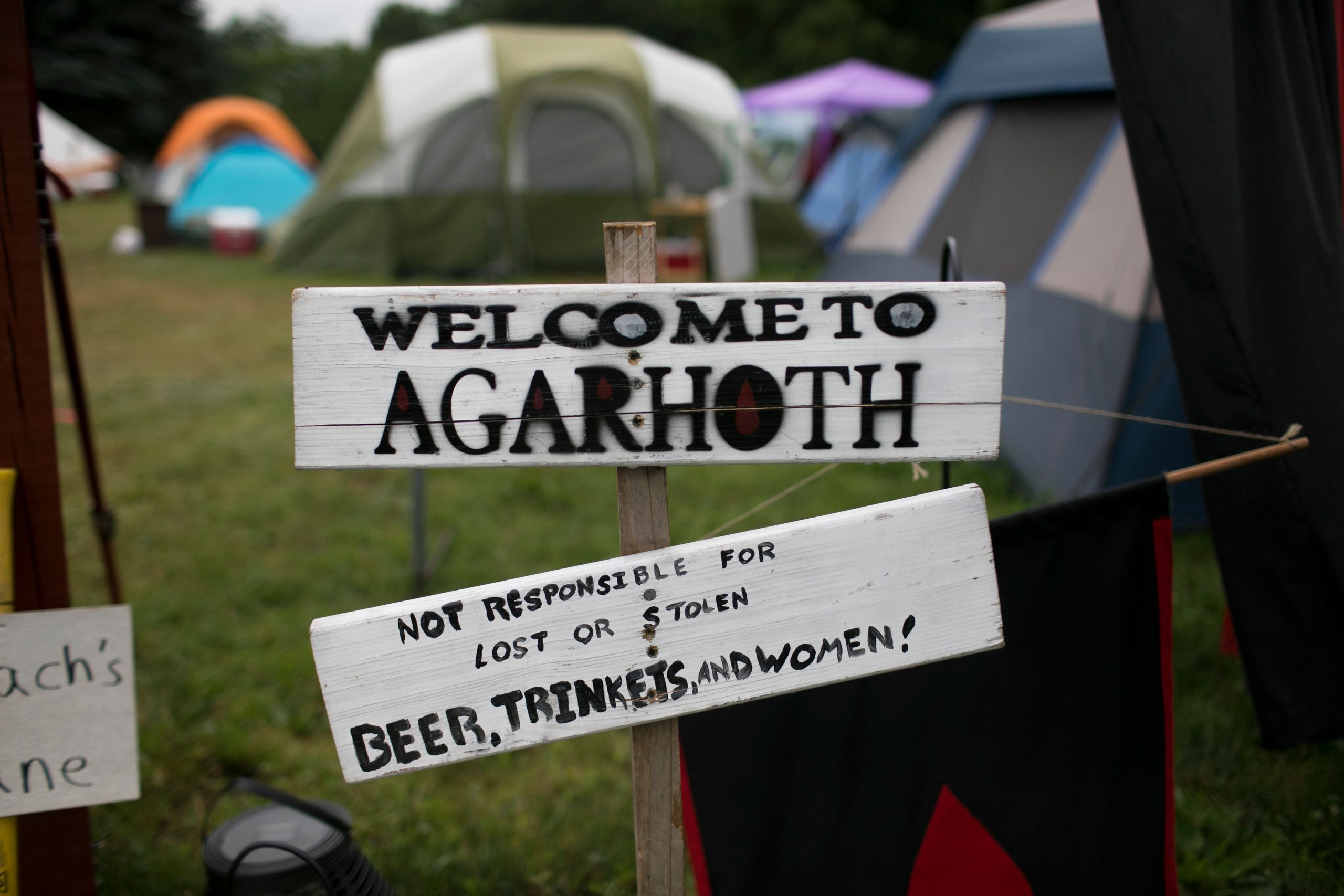 "A ""Welcome to Agarhoth"" sign at a camp entrance."
