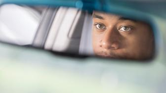 A serious man looks in the rear view mirror of a vehicle.  Only his eyes and nose can be seen.  There is copy space.