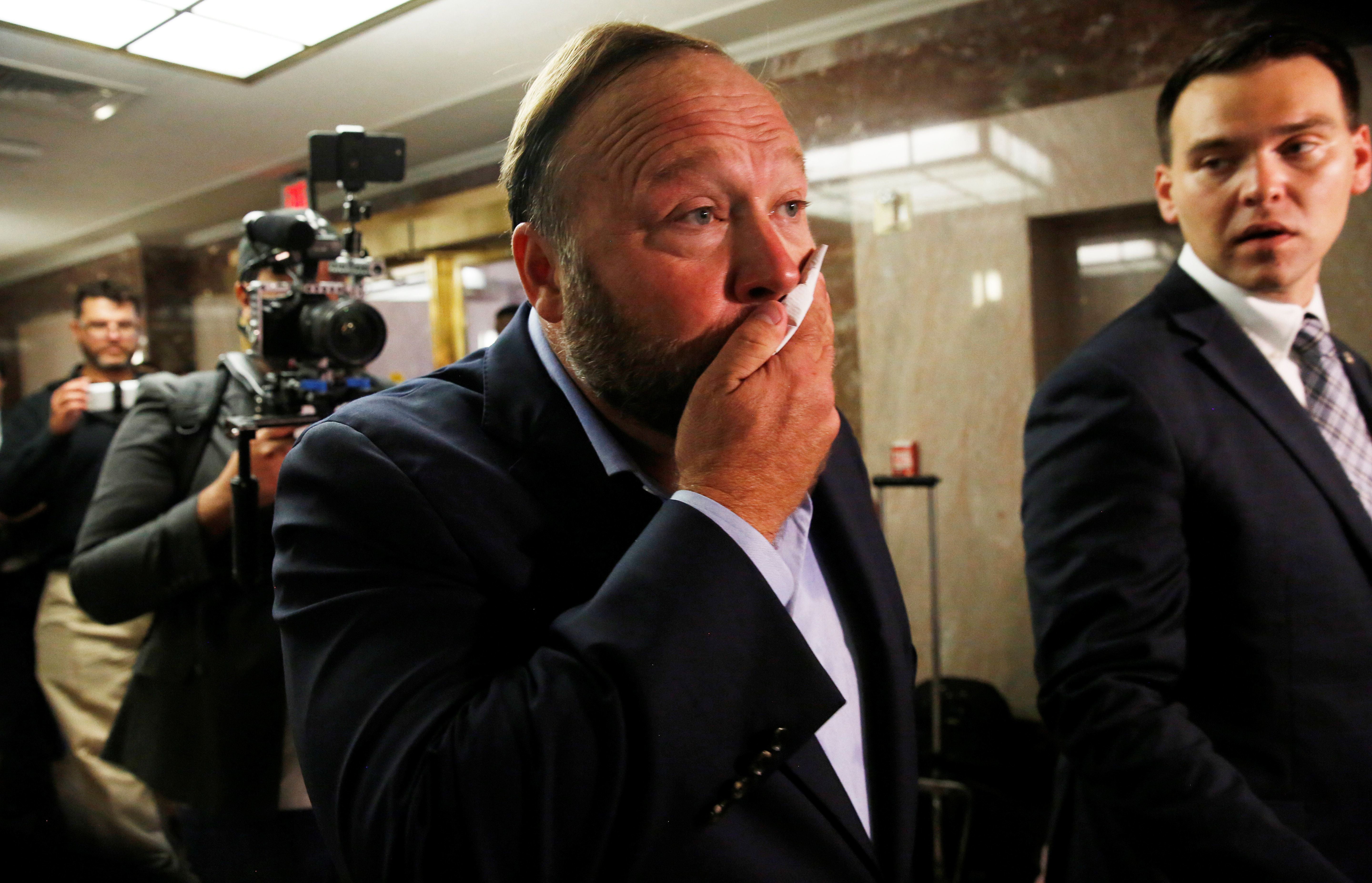 Radio host Alex Jones of Infowars wipes his face after talking to the press as he walks into a Senate Intelligence Committee hearing to listen to Twitter CEO Jack Dorsey and Facebook COO Sheryl Sandberg testify on foreign influence operations on social media platforms on Capitol Hill in Washington, U.S., September 5, 2018. REUTERS/Jim Bourg
