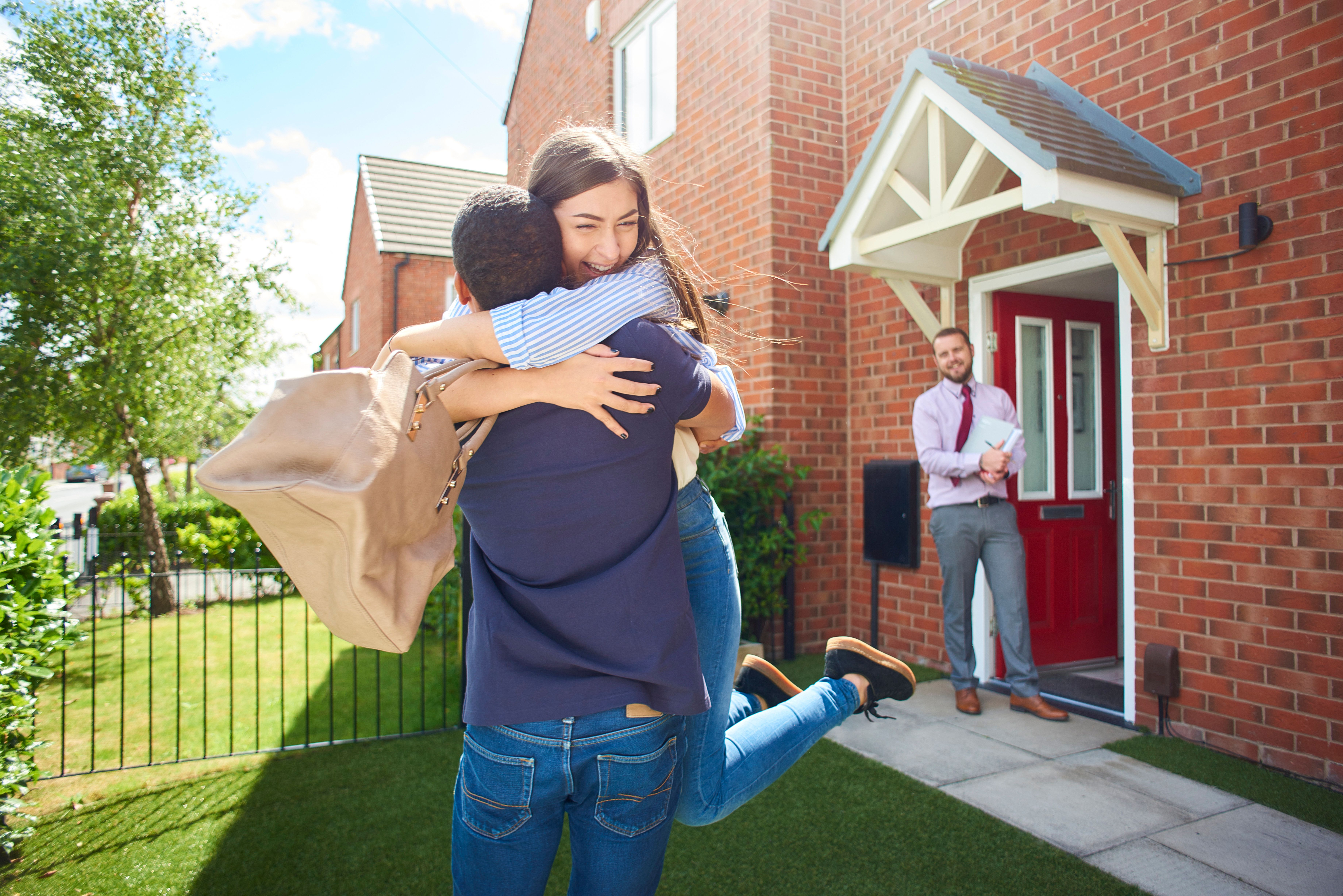 a couple embrace  in front of their new home , in the background an estate agent looks on happily