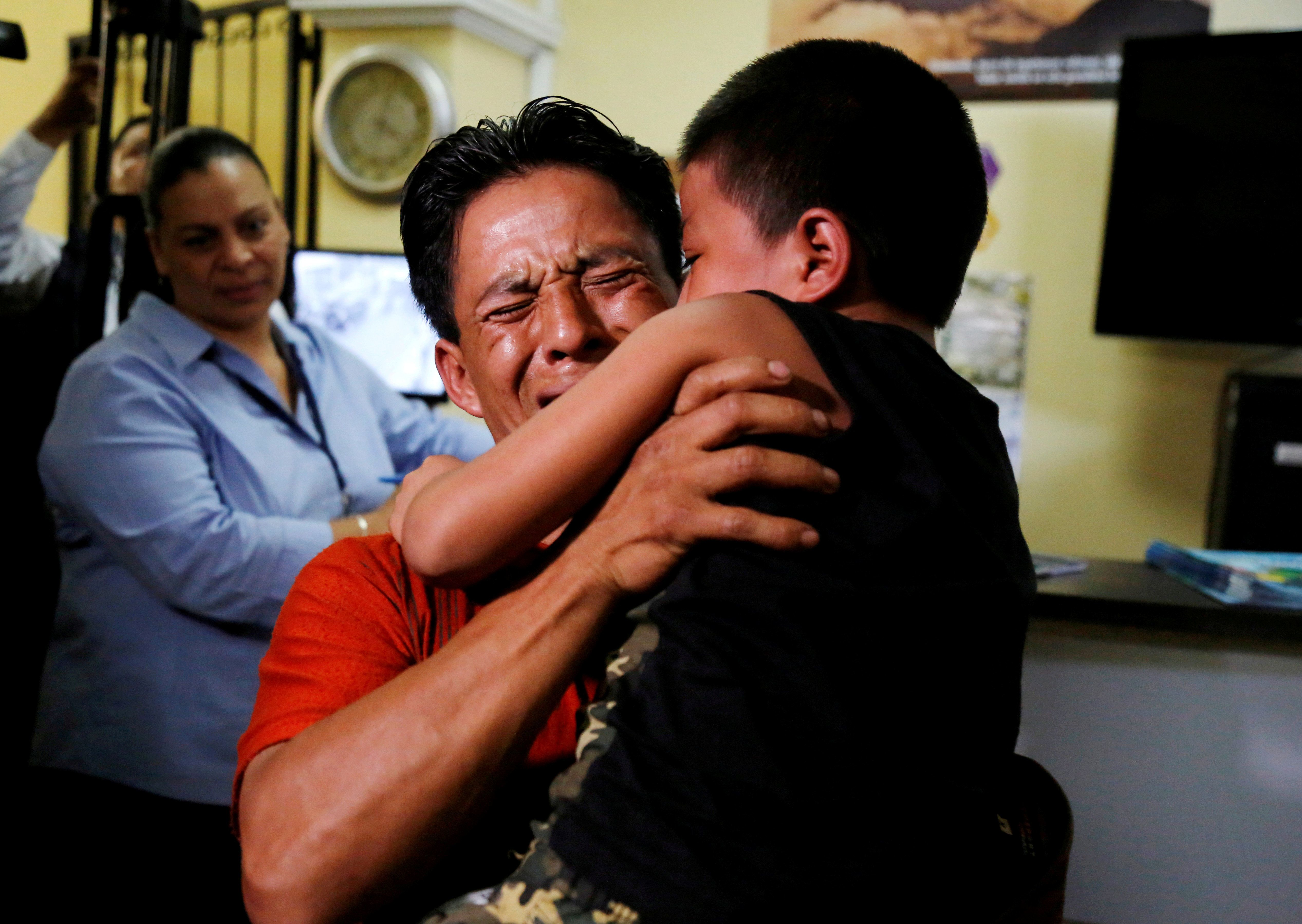 Gilberto Calmo hugs his son Franklin Noe Calmo, who was sent back from detention on Tuesday, after they were separated at the