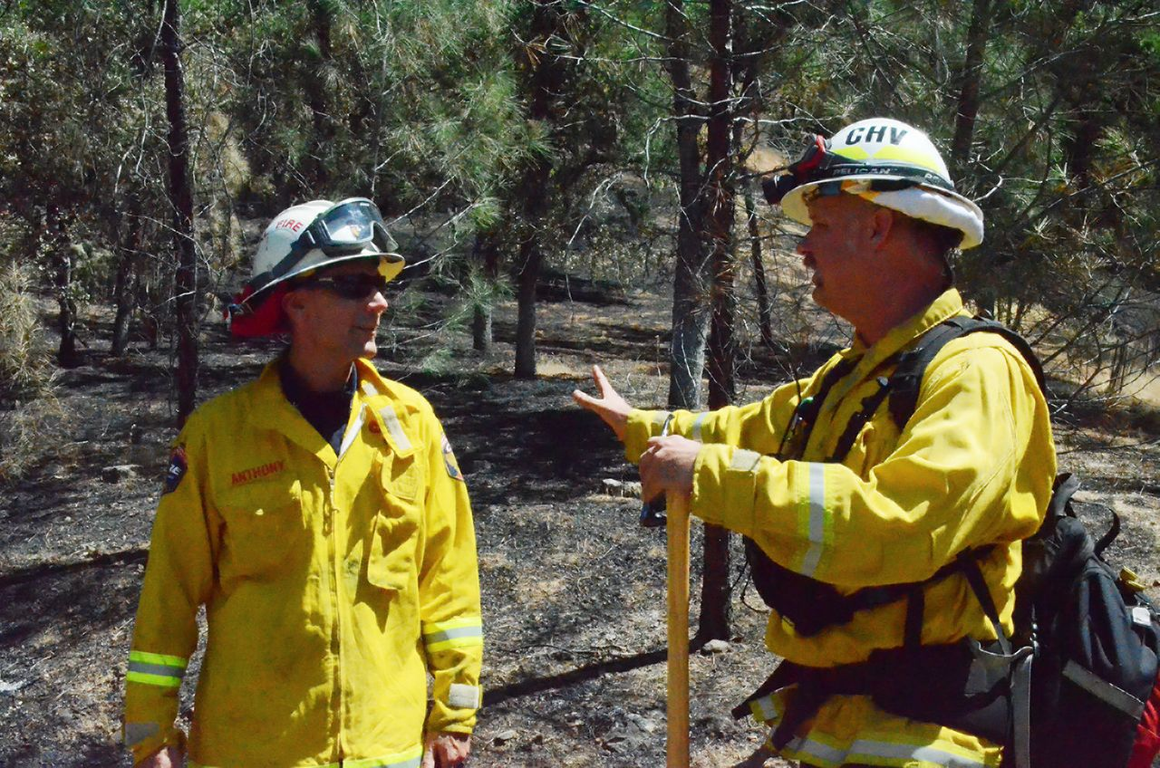 Cal Fire Division Chief Chris Anthony and David Albright, a battalion chief at the Chula Vista Fire Department, visit June 27 on a charred hillside in the Lake County community of Spring Valley, where multiple homes were destroyed by the Pawnee fire.