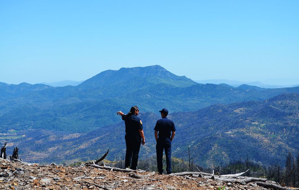 Emily Smith and Chris Anthony, both of Cal Fire, overlook a fire-scarred mountainside in Lake County, California.