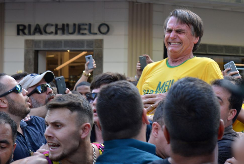 Bolsonaro was riding on the shoulders of supporters when his attacker stabbed him in the abdomen, sending the presidential ca
