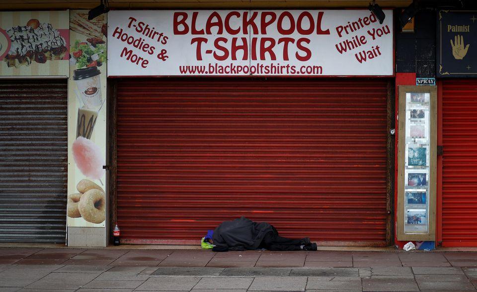 A man sleeps in the doorway of a souvenir shop in