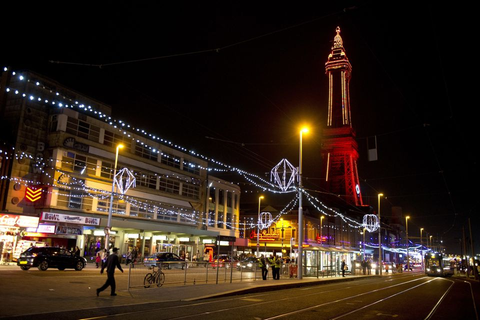 Members of the public admire the Blackpool Illuminations as they walk along the promenade in Blackpool,...