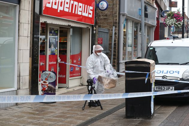 A forensic officer check a bin in Peel Square in Barnsley town centre after the serious