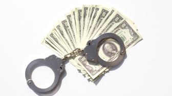 Dirty money or jail? Daylight shooting of police clamp and a stack of money.