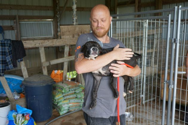 An ASPCA rescuer carries one of the dogs found on the