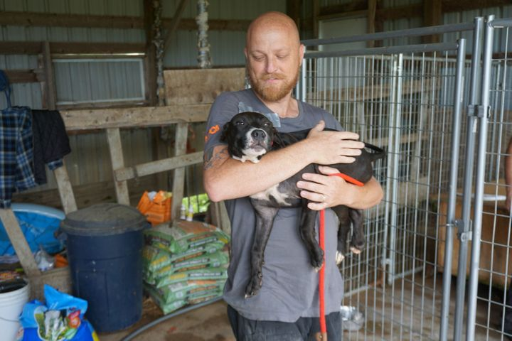 An ASPCA rescuer carries one of the dogs found on the property.