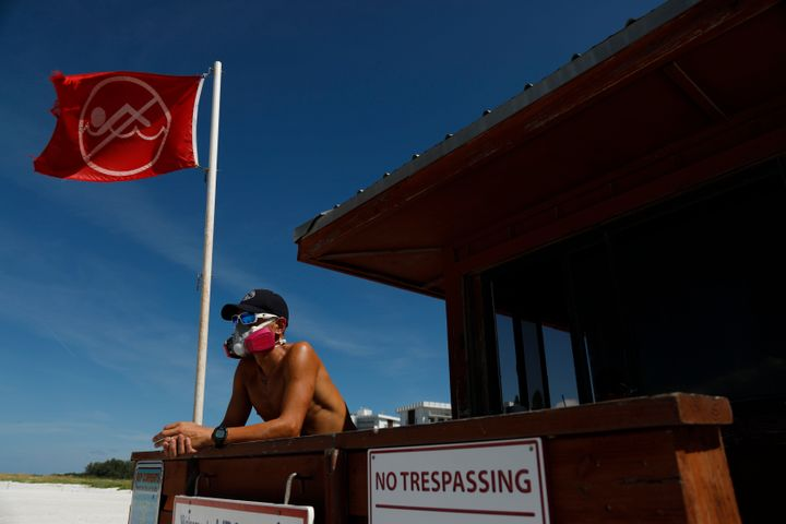 Sarasota County Emergency Services lifeguard Mariano Martinez wears a mask because of red tide at Lido Beach on Aug. 26.