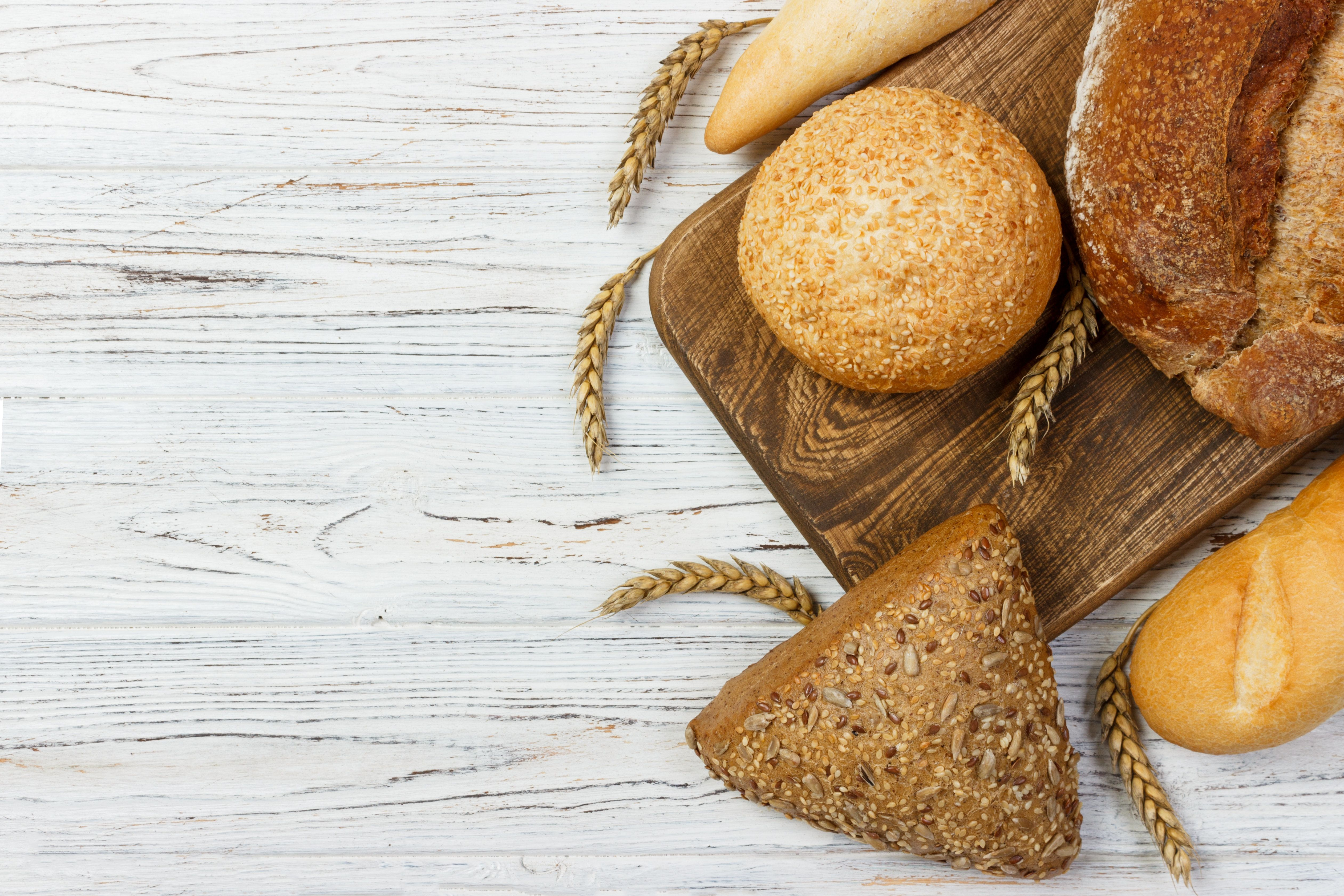 Bread and wheat on white wooden background.