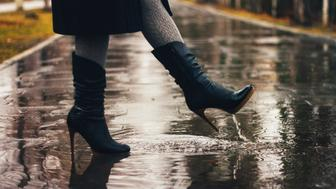 Female legs and women leather boots in the rain.