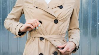 Female hand tie belt on a coat outdoors