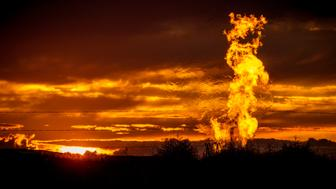 Flames from a flaring pit near a well in the Bakken Oil Field. The primary component of natural gas is methane, which is odorless when it comes directly out of the gas well. In addition to methane, natural gas typically contains other hydrocarbons such as ethane, propane, butane, and pentanes. Raw natural gas may also contain water vapor, hydrogen sulfide (H2S), carbon dioxide, helium, nitrogen, and other compounds. (Source: www.earthworksaction.org). As of July 2014, roughly 30 percent of the (Photo by Orjan F. Ellingvag/Corbis via Getty Images)