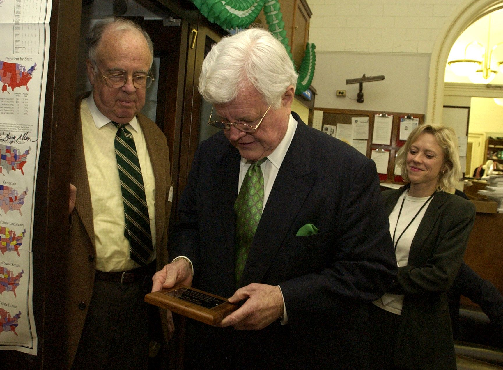 UNITED STATES - MARCH 17:  Sen. Ted Kennedy, D-Mass., inspects a plaque that was dedicated to the late Mary McGrory and was hung in the Senate Press Gallery. Adam Clymer, former New York Times reporter, appears at left, and Judy Holland of Hearst, at right.  (Photo By Tom Williams/Roll Call/Getty Images)