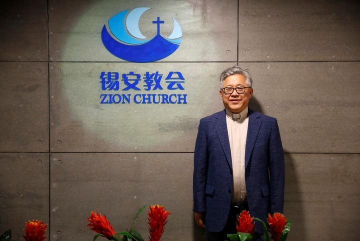 "Jin Mingri, head pastor of Beijing's Zion church, poses in the lobby of the unofficial Protestant ""house"" church on August 28"