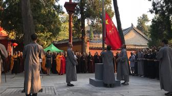 ZHENGZHOU, CHINA - AUGUST 27: Monks raise the Chinese national flag during the first national flag raising ceremony at Shaolin Temple at Mount Song on August 27, 2018 in Zhengzhou, Henan Province of China. Shaolin Temple holds on Monday its first national flag raising ceremony since its establishment in 495 in Zhengzhou. (Photo by VCG/VCG via Getty Images)