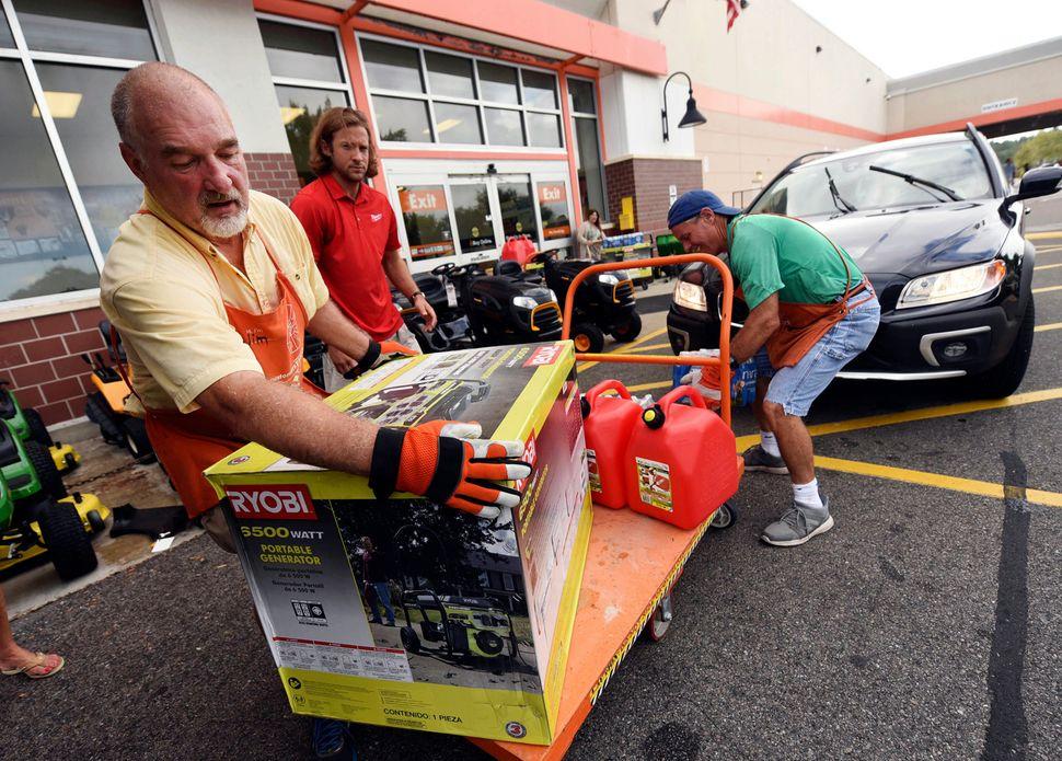 Jim Craig, David Burke and Chris Rayner load generators as people buy supplies at The Home Depot in Wilmington, North Carolin