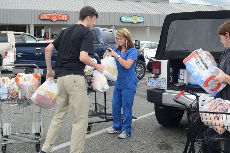 From left, Douglas Hill loads groceries into Wendy Cannon's jeep as she and Logan Coombs, right, purchased items from the Pig