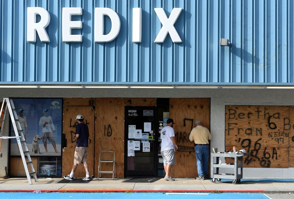 Employees of Redix board up the front windows of the store in Wrightsville Beach, North Carolina, on Tuesday.