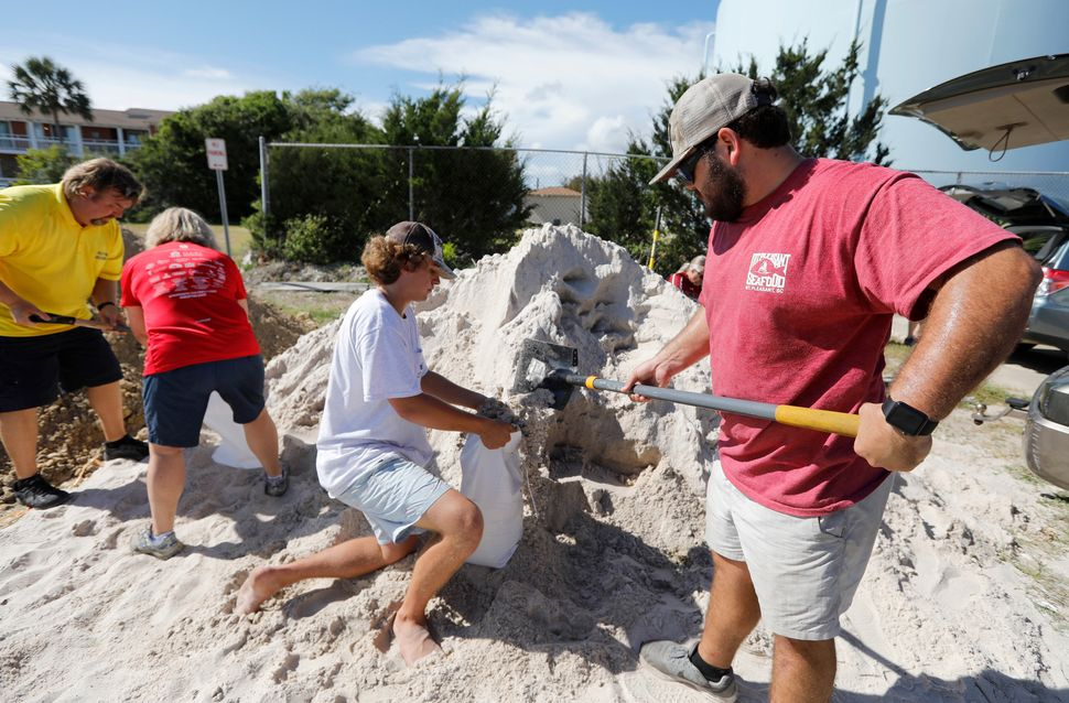 Walker Townsend, at right, from the Isle of Palms, South Carolina, fills a sandbag while Dalton Trout, in center, holds the b