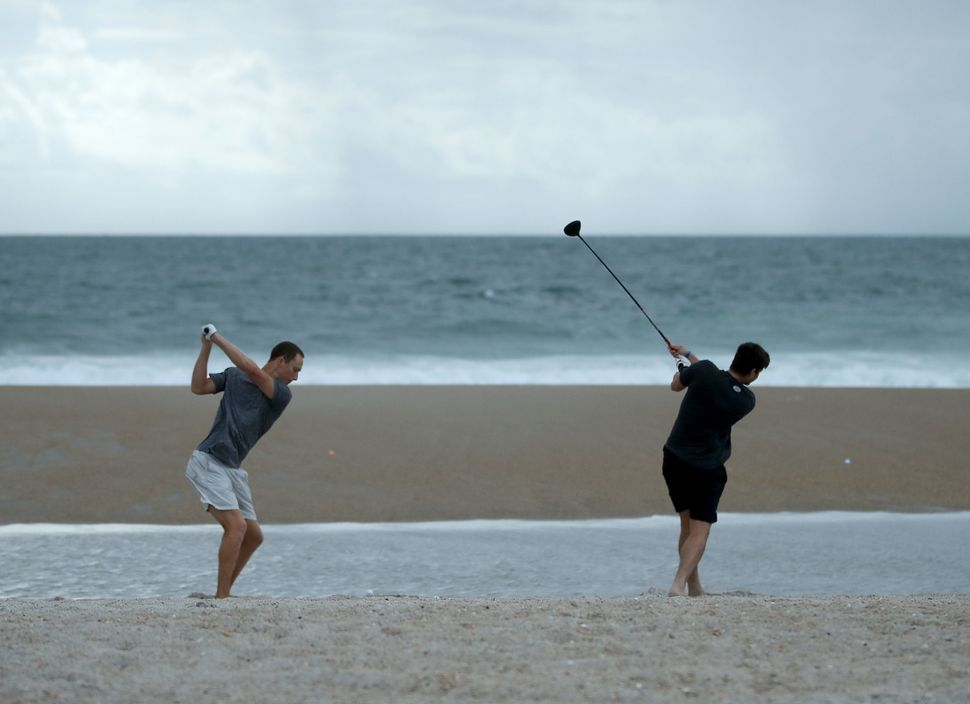 Jacob Whitehead (L) and Matt Jones hit golf balls into the surf in Wrightsville Beach on Sept. 11 as Hurricane Florence appro