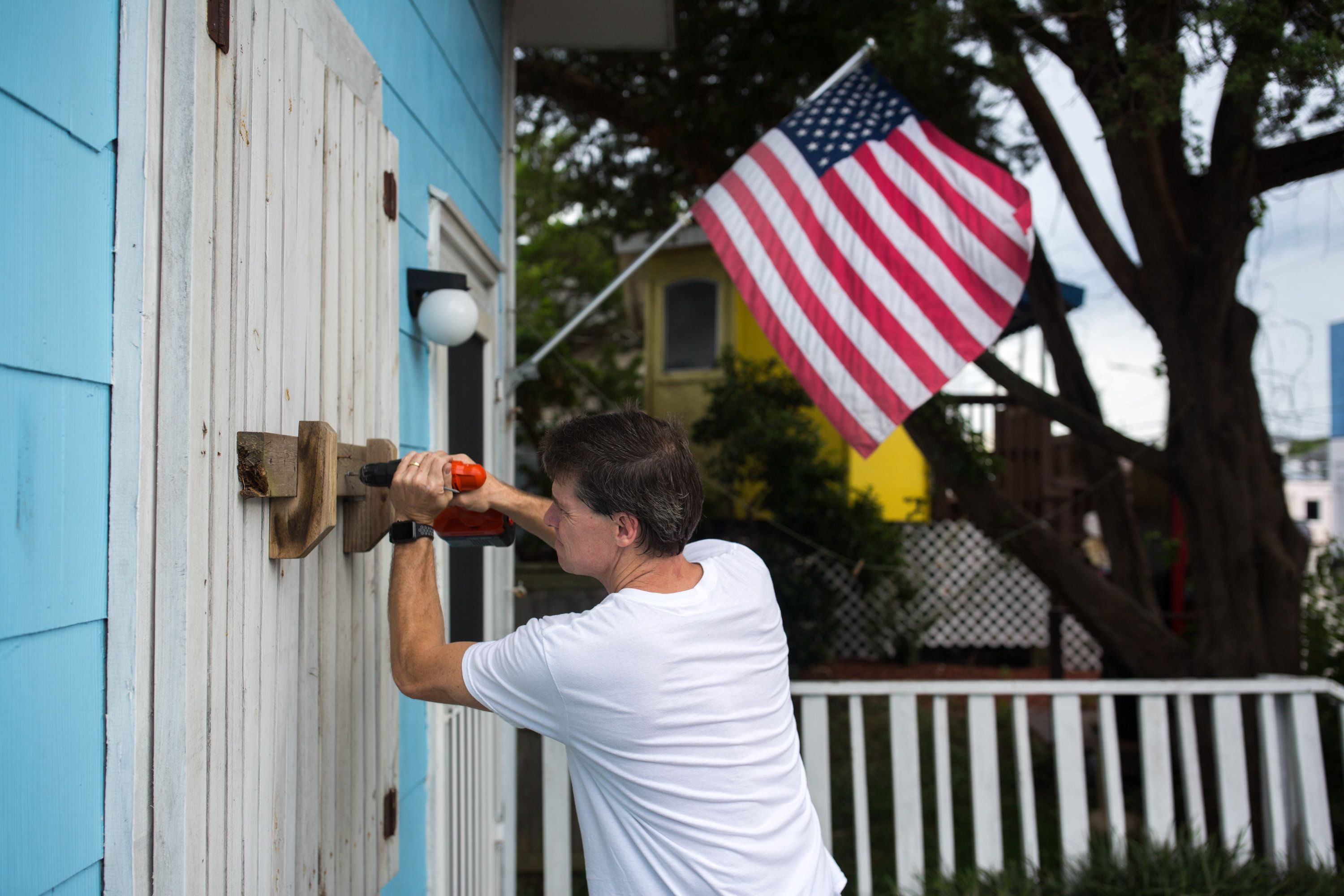 A man helps board up Aussie Island surf shop on Sept. 11, 2018, in Wrightsville, North Carolina.