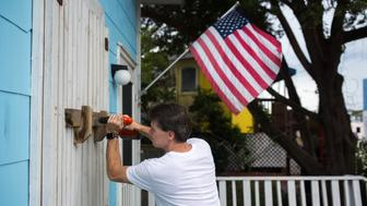 A man helps board up Aussie Island surf shop on September 11, 2018 in Wrightsville, North Carolina in anticipation of Hurricane Florence's high storm surge. - More than a million people were under evacuation orders in the eastern United States Tuesday, where powerful Hurricane Florence threatened catastrophic damage to a region popular with vacationers and home to crucial government institutions. (Photo by Logan CYRUS / AFP)        (Photo credit should read LOGAN CYRUS/AFP/Getty Images)