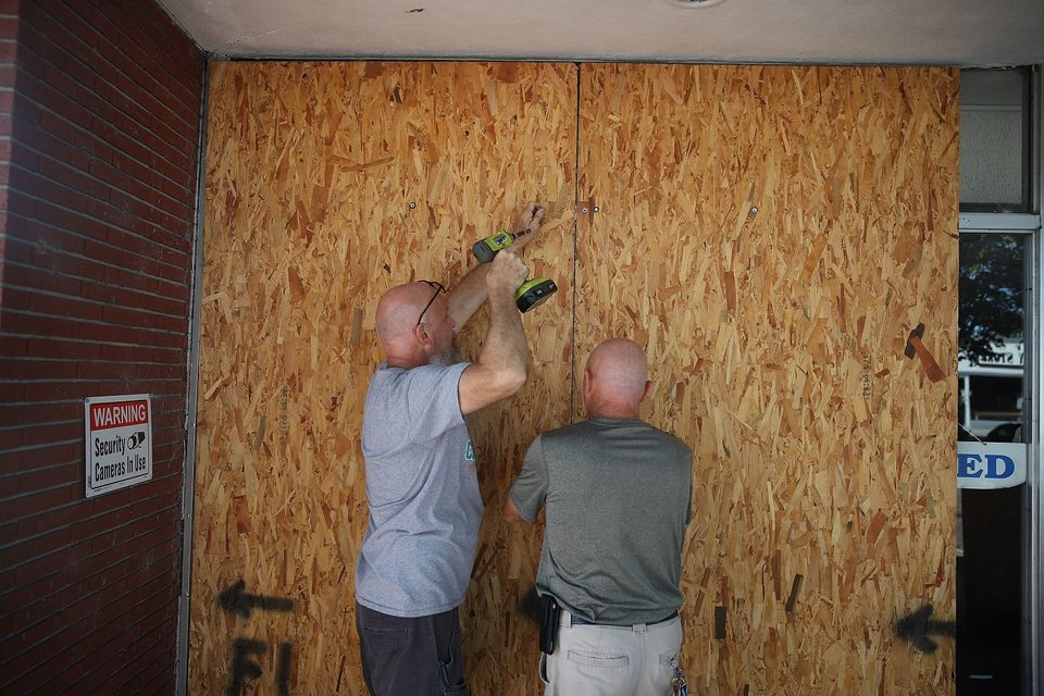 Jay Schwartz (L) and Michael Schwartz secure plywood over the windows of their business ahead of the...