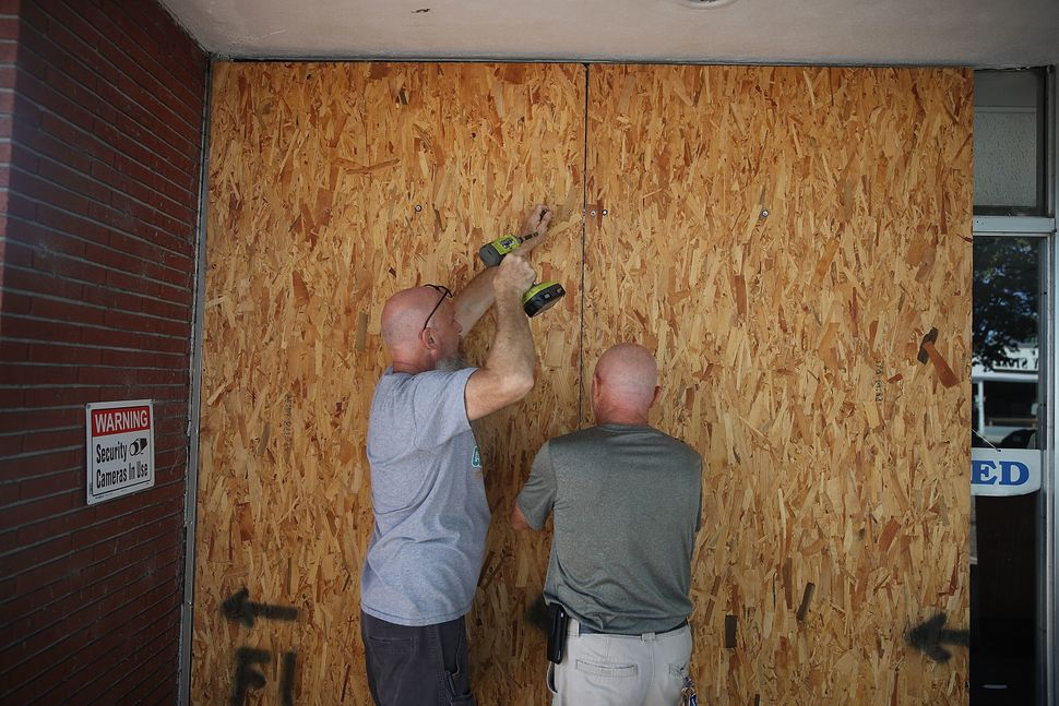 Jay Schwartz, left, and Michael Schwartz secure plywood over the windows of their business ahead of the arrival of Hurricane