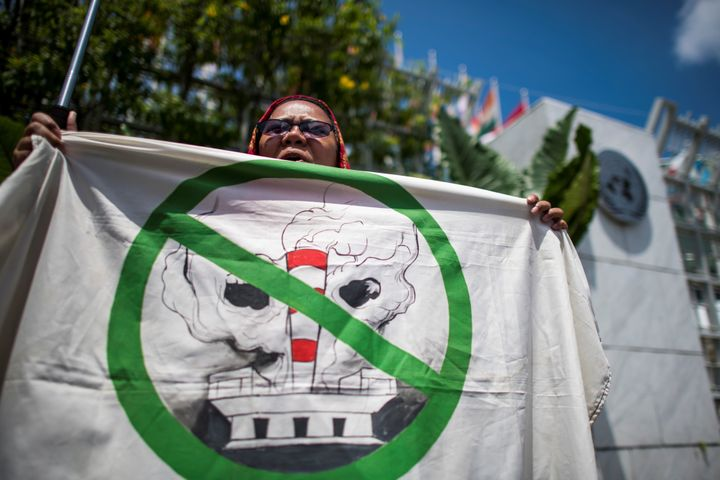 An environmental activist shouts slogans during a demonstration in front of the United Nations building in Bangkok on Sept. 7