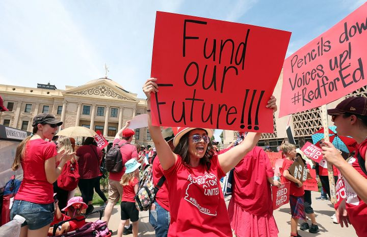An Arizona teacher holds up a sign in front of the state capitol in Phoenix on April 26.