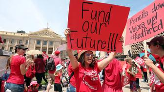 PHOENIX, AZ - APRIL 26:  An Arizona teacher holds up a sign in front of the State Capitol during a #REDforED rally on April 26, 2018 in Phoenix, Arizona. Teachers state-wide staged a walkout strike on Thursday in support of better wages and state funding for public schools.  (Photo by Ralph Freso/Getty Images)