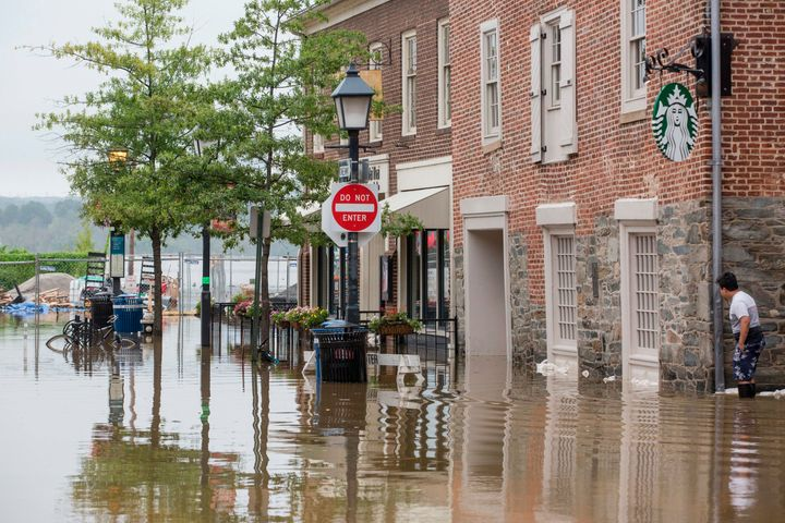Heavy rain flooded the streets of Old Town Alexandria, Virginia, on Tuesday as sandbags were being distributed to businesses