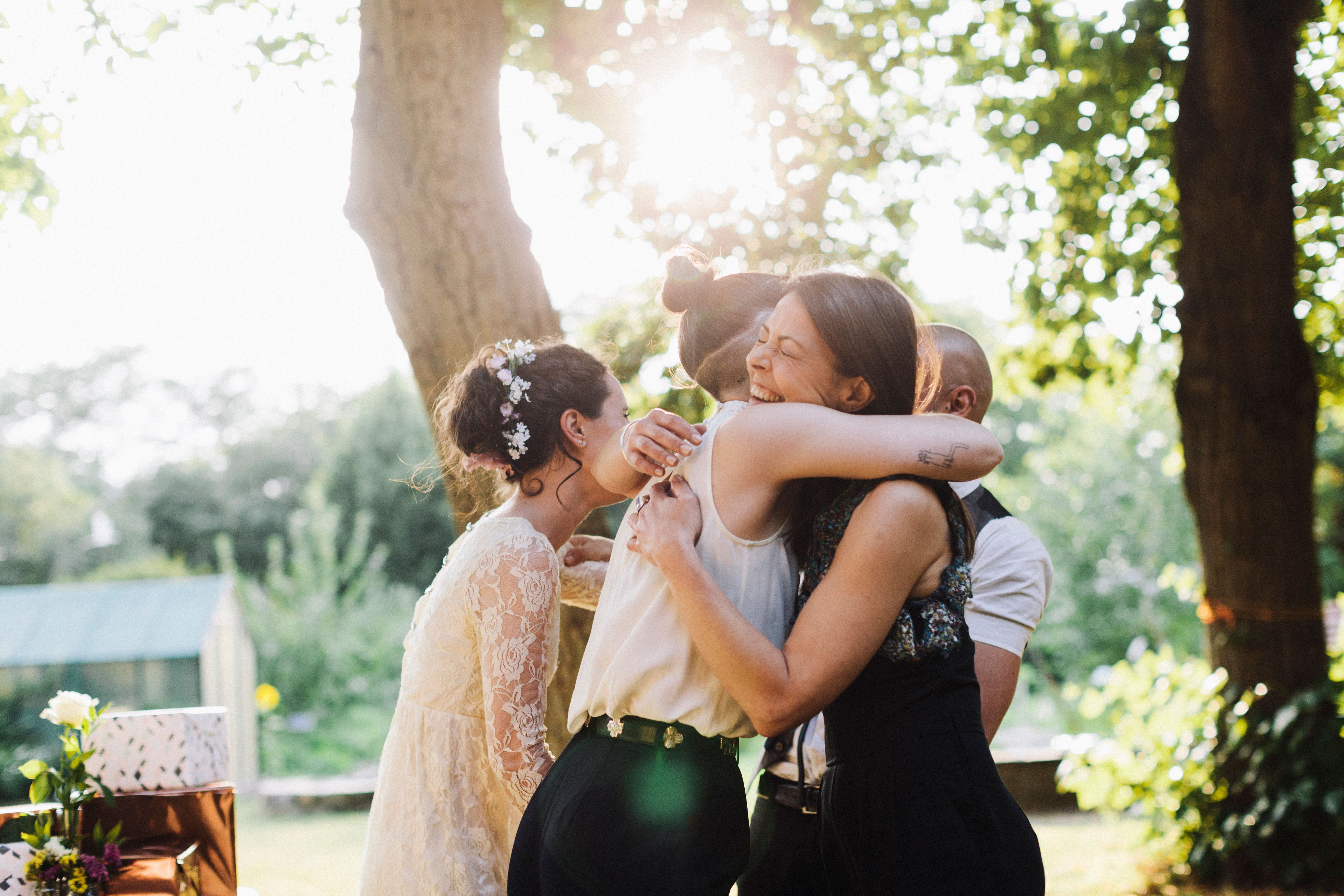 Newlywed lesbian couple being congratulated by wedding guest.
