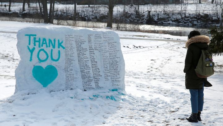 """A Michigan State University student stops to look at """"The Rock"""" painted with the names of survivors of Larry Nassar in East L"""