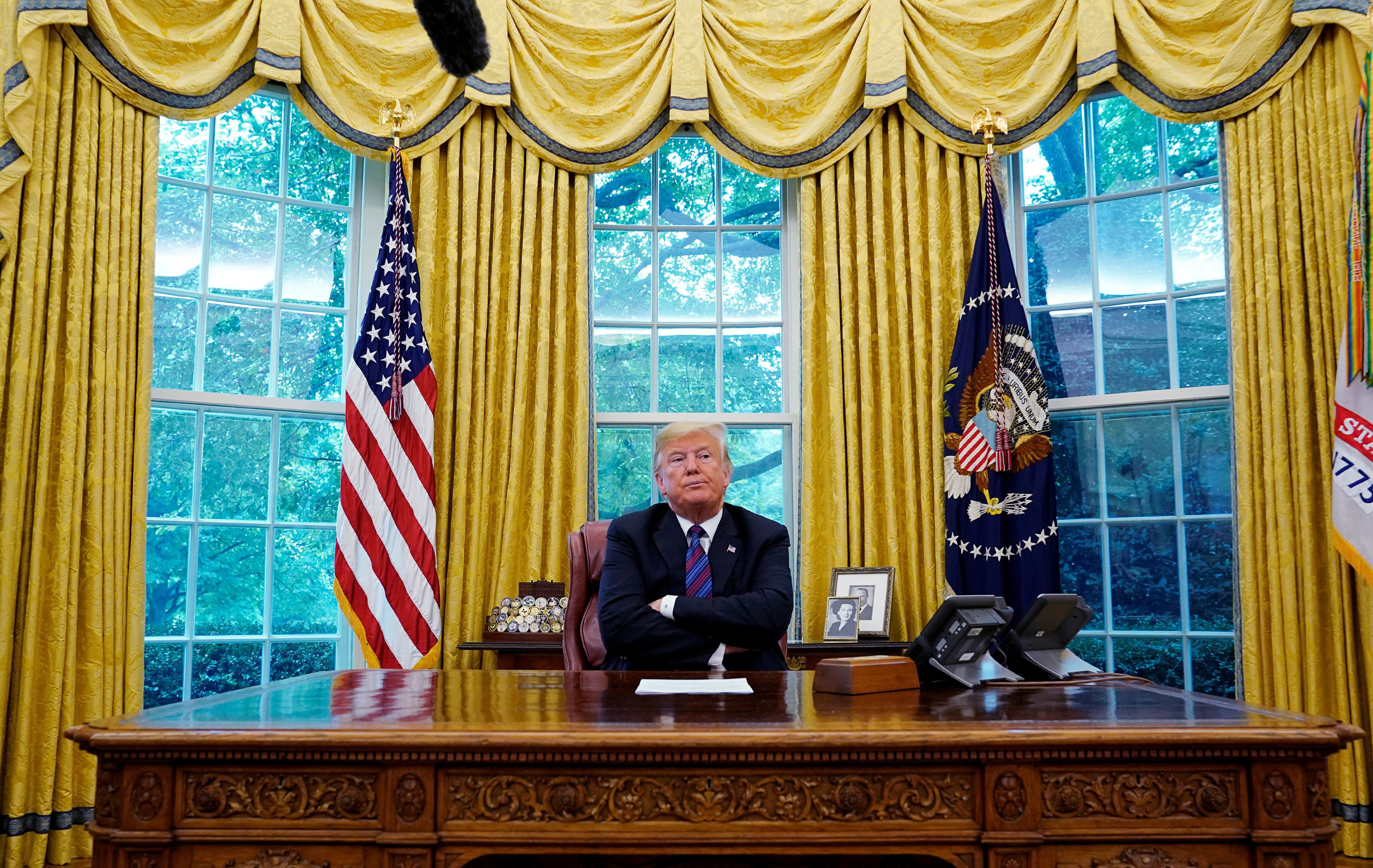U.S. President Donald Trump sits behind the Resolute desk as he makes an announcemment on the status of the North American Free Trade Agreement (NAFTA) from the Oval Office of the White House in Washington, U.S., August 27, 2018. REUTERS/Kevin Lamarque