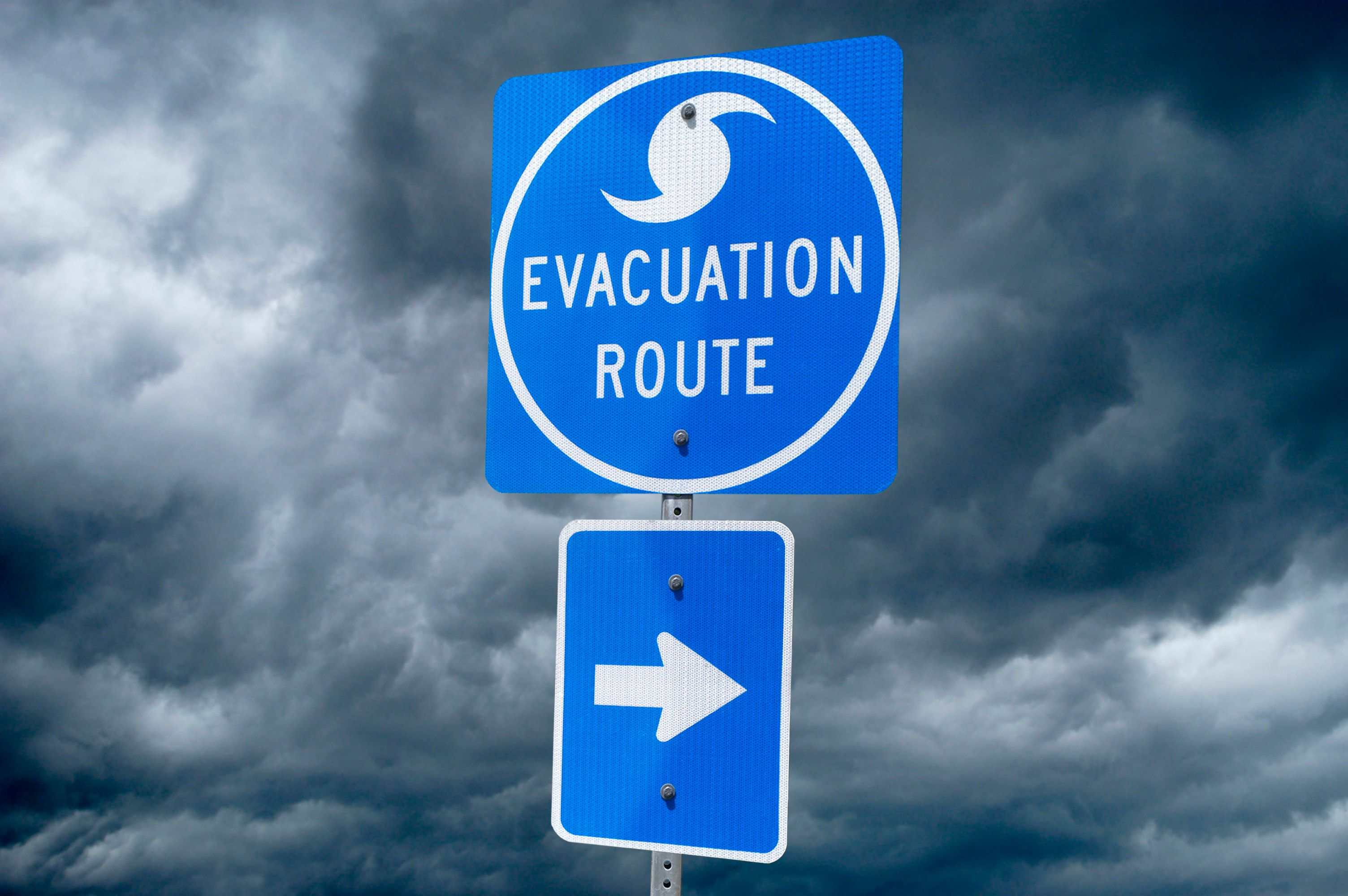 A Directional Sign in Front of Storm Clouds indicating the Storm Evacuation Route. Arrow on sign is directing to the right.