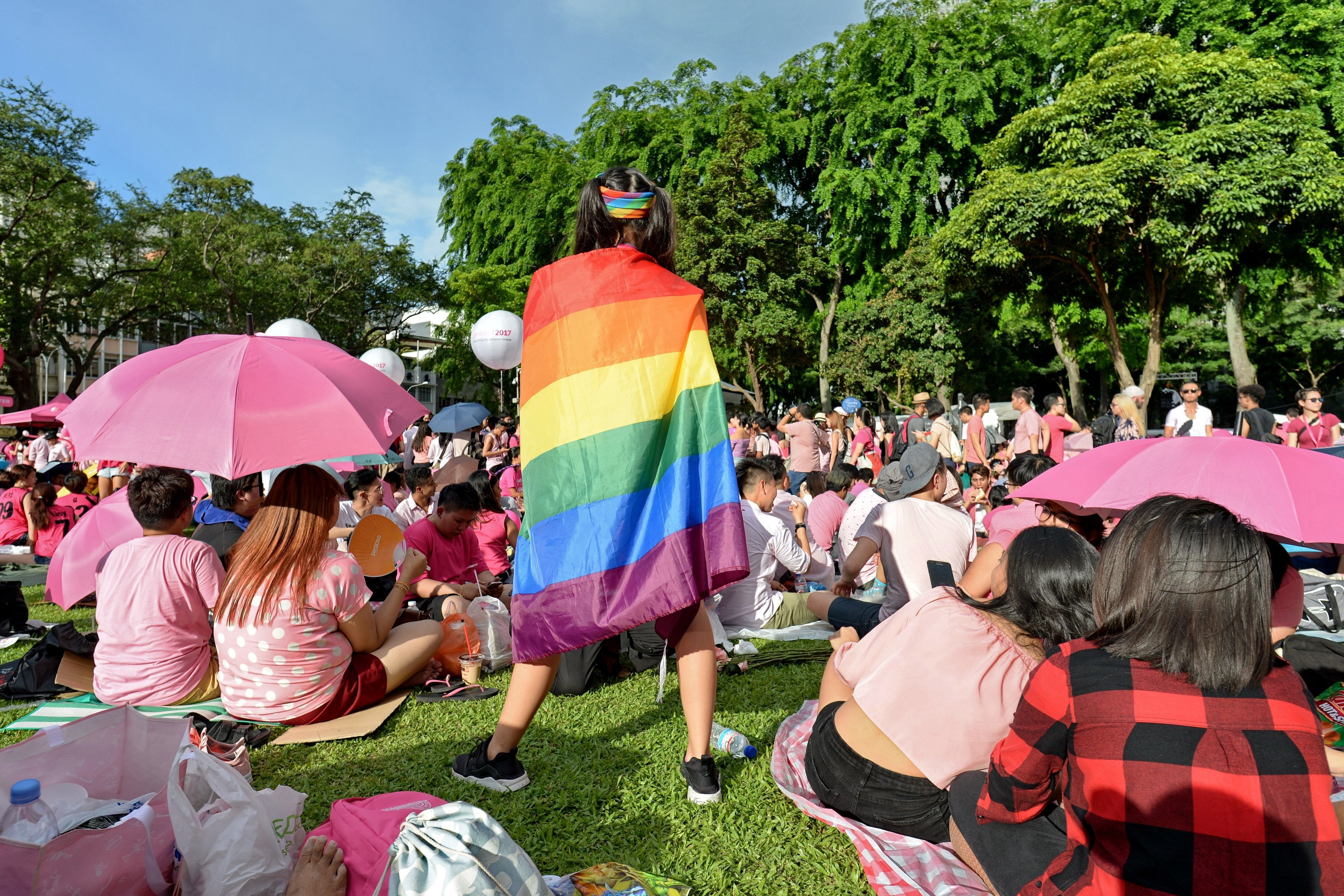 A supporter wrapped in a rainbow flag attends the annual 'Pink Dot' event in a public show of support for the LGBT community at Hong Lim Park in Singapore on July 1, 2017.  Thousands of Singaporeans took part in the gay-rights rally on July 1. / AFP PHOTO / Roslan RAHMAN        (Photo credit should read ROSLAN RAHMAN/AFP/Getty Images)